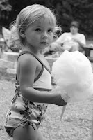 A toddle girl walking with cotton candy at a birthday party
