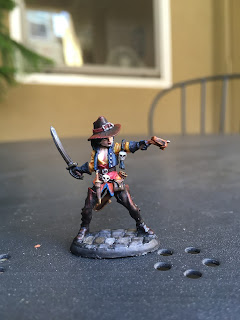 front view of a painted miniature woman figure pointing a crossbow and brandishing a sword