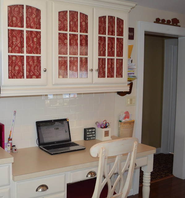 Red fabric on glass cabinets over kitchen desk