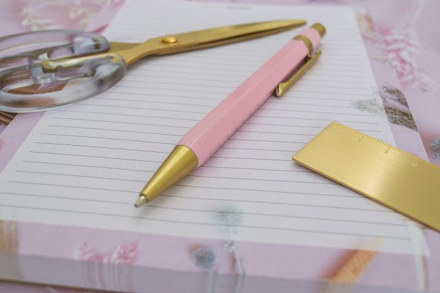 Gold and pink ballpoint pen laying on a notebook