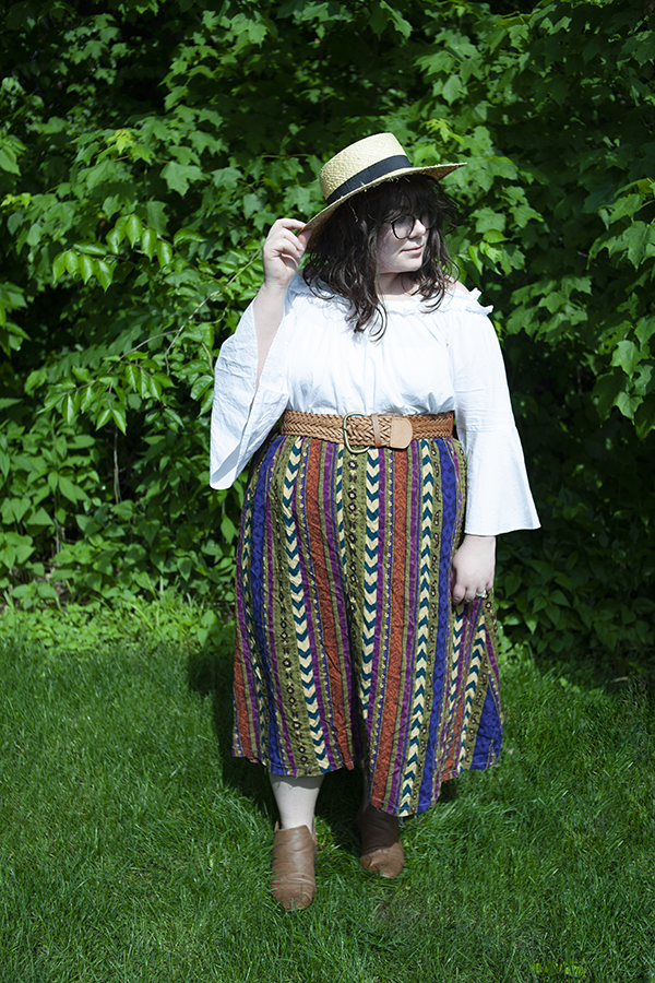 An outfit consisting of a large straw sunhat, white ruffle off the shoulder blouse, a printed maxi skirt, and brown booties.