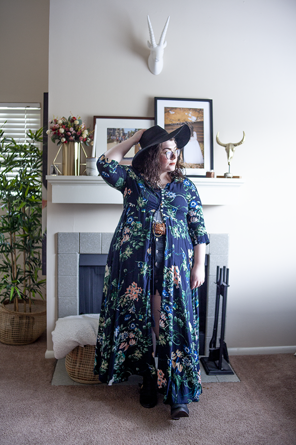 An outfit consisting of an oversized black floppy fedora, a dark blue floral button down maxi dress, with only the bodice buttoned, a white lace blouse tucked into a black button down skirt, and black heeled buckle closure boots.