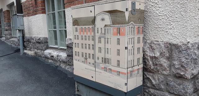 Kadulla oleva sähkökaappi, johon on maalattu yksityiskohtainen kuva kerrostalosta