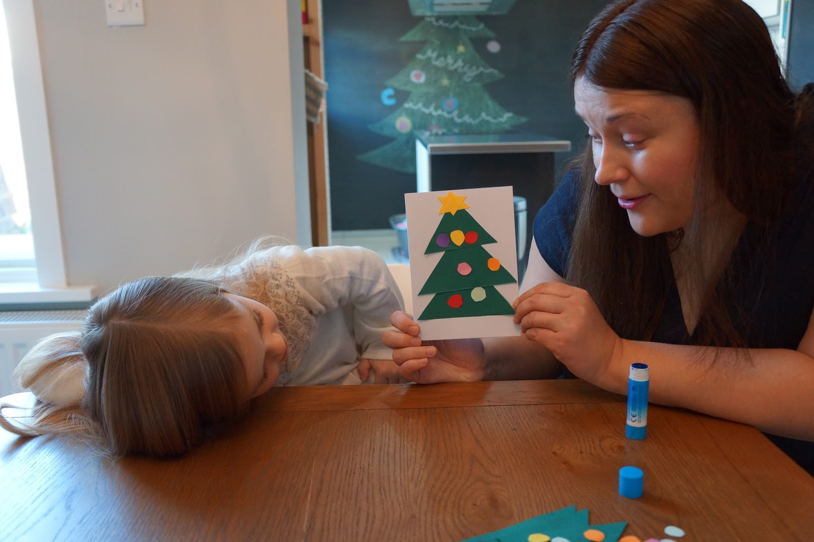 mum showing a christmas tree card to a young daughter