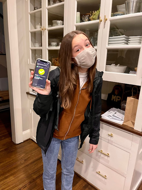 teen in a mask holding her phone