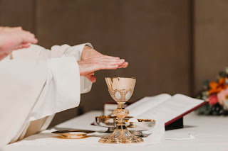 Priest with hands over the chalice