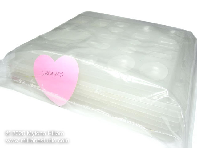 A stack of sprayed plastic mould trays inside a ziplock bag