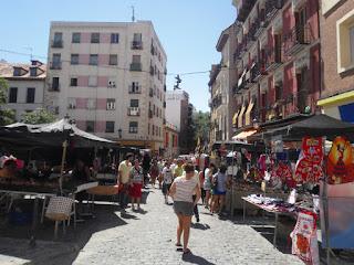 Artículos textiles de todo tipo en puestos de vendedores cubiertos por sombrillas para protegerlos del sol.