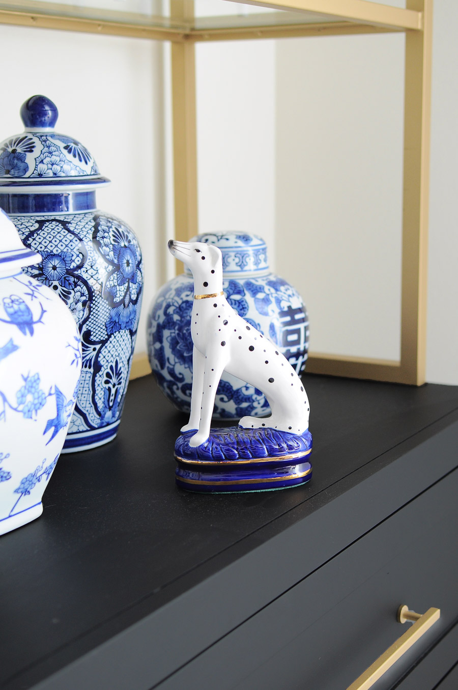 Fitz and Floyd Dalmatian Bookend paired with gorgeous ginger jars on a black and gold bookcase.