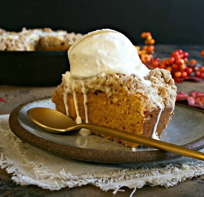 Recipe for a pumpkin cake with a crumb topping, served with honey vanilla ice cream swirled with honeycomb.