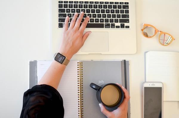 Flatlay mãos femininas segurando xícara de café enquanto mexe no notebook