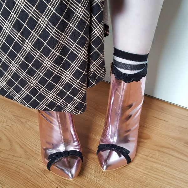 close up of feet in pink metallic boots with small black bow and mesh socks