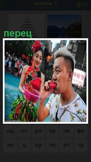 на улице женщина предлагает мужчине съесть перец красный
