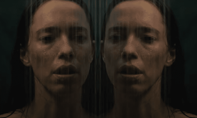 Double close up image of a woman's face in a shower door
