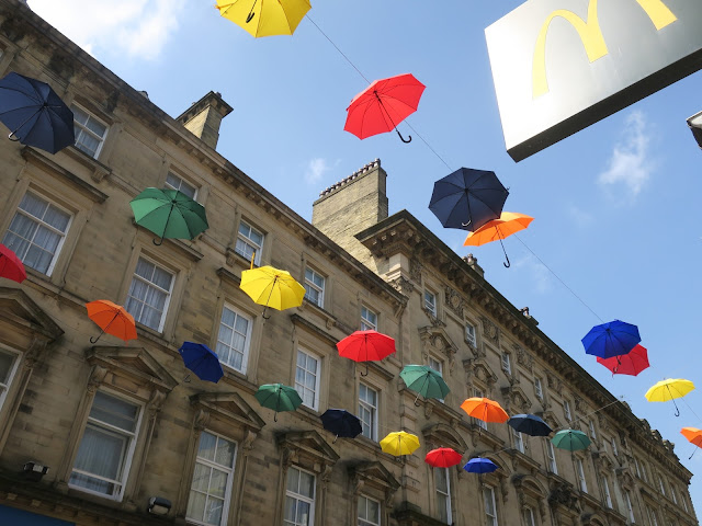 Umbrellas decorating Halifax for Le Tour de Yorkshire: red, yellow, blue, green, orange,
