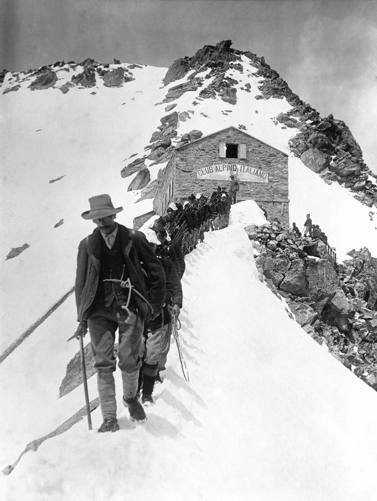 Members of an Italian alpine regiment leave a stone hut high in the Alps. 1915.