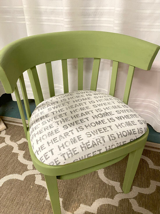 Green antique chair with black and white font fabric