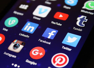 A photo of a smartphone screen with icons for social media apps showing, including LinkedIn, Facebook, Twitter, Instagram, Tumblr, Pinterest and Myspace