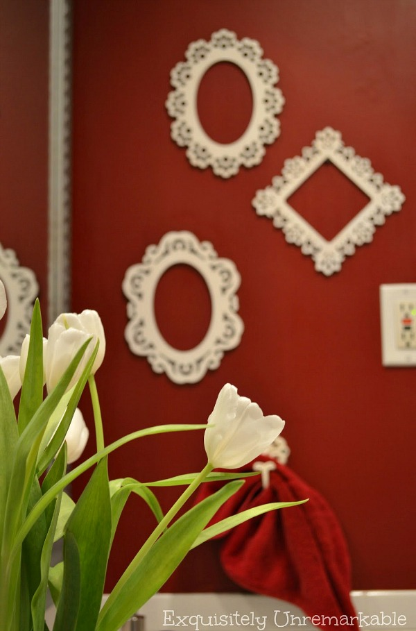 Flowers In The Bathroom with white wooden frames hanging on a red wall