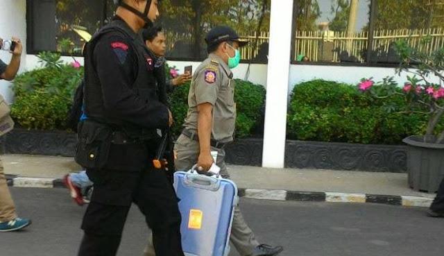 Seorang petugas dikawal personel Brimob membawa koper setelah penggeledahan di kantor Dinas Peternakan Jawa Timur di Surabaya pada Rabu, 7 Juni 2017