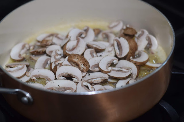 Sliced mushrooms in a pan on the stove.