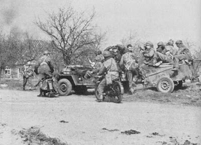 Wartime photo shows motorcycles and Jeep with airborne soldiers.