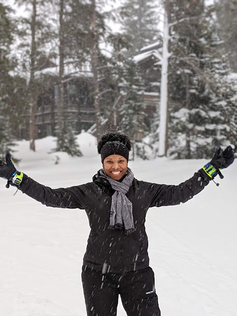 young black woman smiling in the snow with huge cabin in the background
