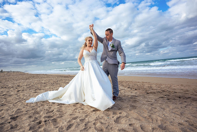 Bride and groom twirling on the beach