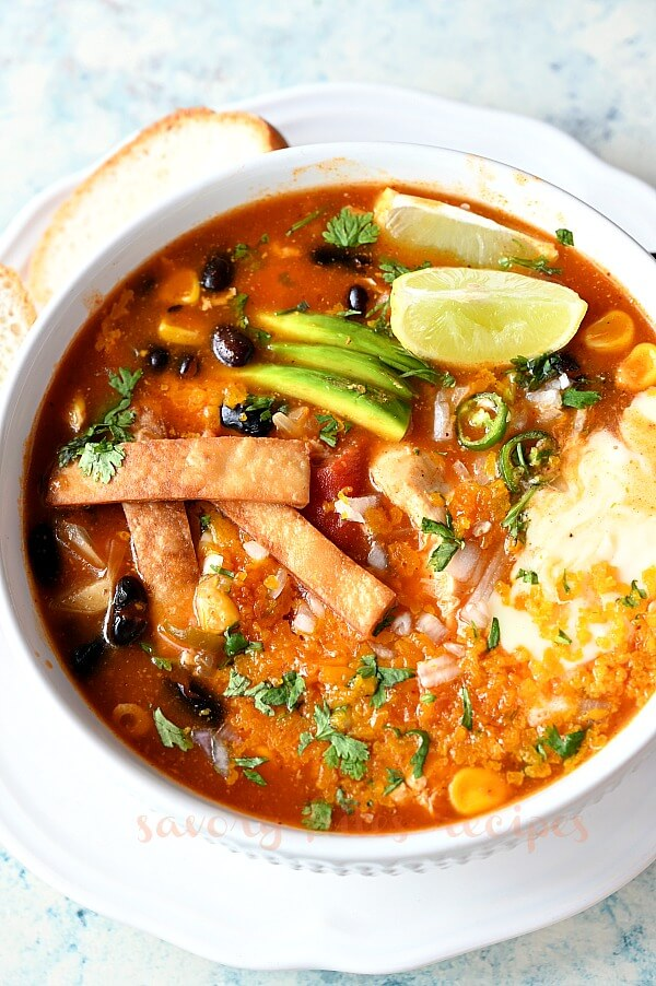 enchilada soup with lemon wedges,avocado slices and tortilla strips