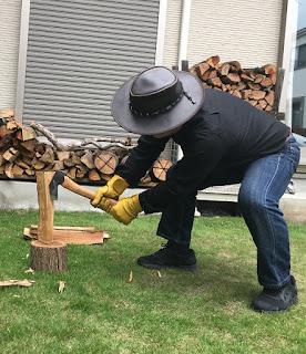両手で斧をもって、薪を台に叩きつける