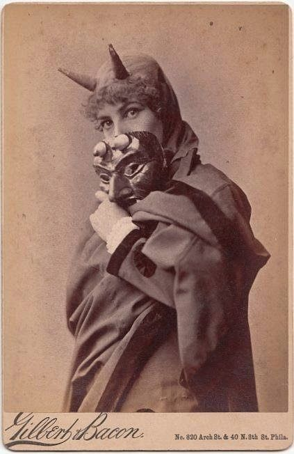 Vintage photo. Actress dressed as the devil peeks over the top of her devil mask. Early 1900s.  Redbad Standards and Other Stories of Hell. marchmatron.com