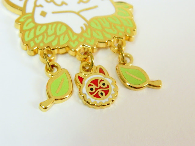 A photo showing charms on an enamel pin by PokoPins, two leaves and a Mononoke mask