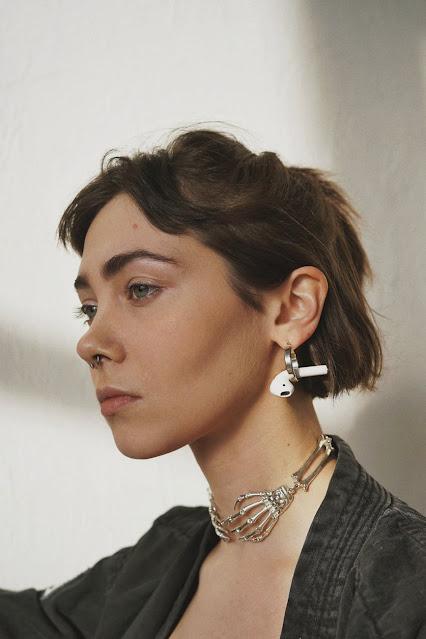 Brunette woman wearing a skeleton choker necklace.