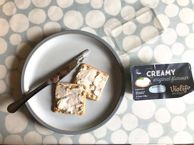 crackers on a plate spread with Violife creamy with a packet next to them