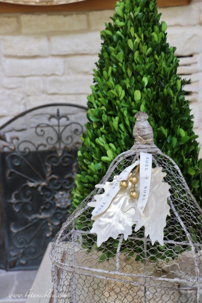 a made over gold berry leaves ornament atop a wire birdcage looks great with a boxwood topiary for Christmas