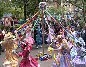 Girls in multi-colored dresses dance around a Maypole at a festival.