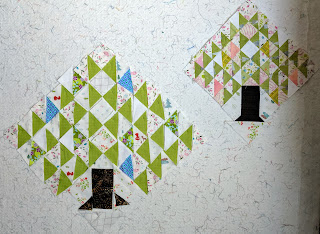Two pine tree quilt blocks. One with all the fabric laid out as leaves, trunk and background. The other with all the pieces sewn. This highlights how much sewing contracts the blocks.