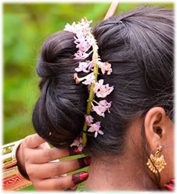 A girl wearing Foxtail Orchid around her bun