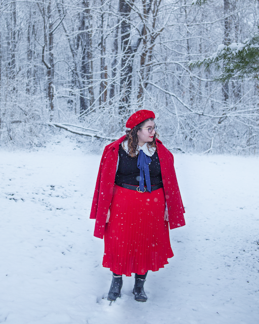 An outfit consisting of a red beret, red coat draped over the shoulders of an oversized white peter pan collar under a black sleeveless dress under a red pleated midi skirt and Doc Marten Lenore chelsea boots.