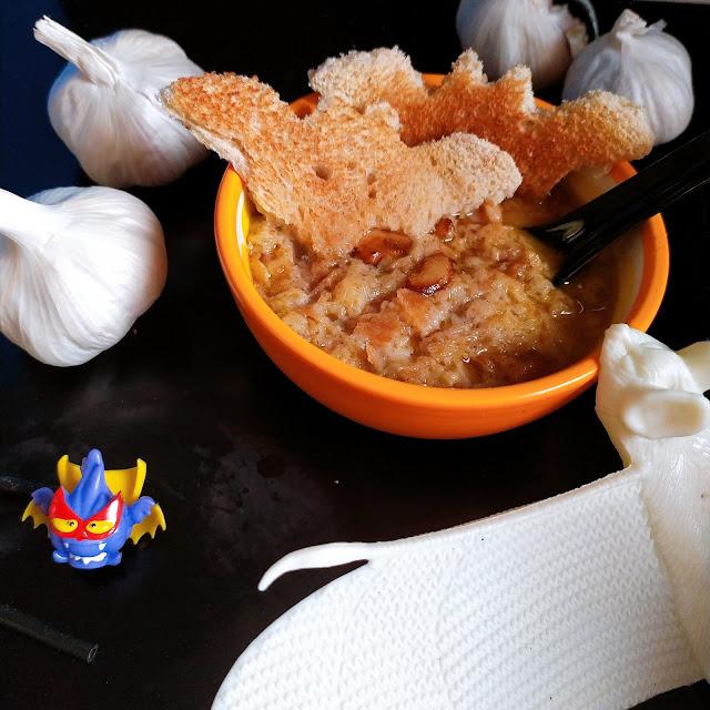 Ajos y una figura superzing de un ajo vampiro junto a un cuenco naranja con dos tostadas cortadas en forma de murciélago y una sopa de Ajo