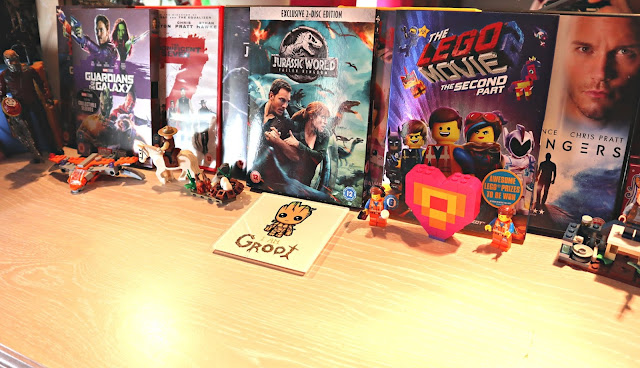A row of DVDs, with various Lego figures and small toys displayed in front