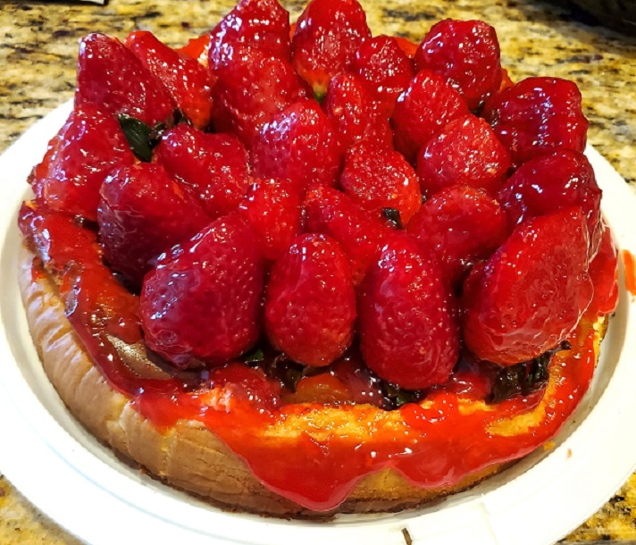 this is a cheesecake ny style on a plastic cake tray with whole glazed strawberries on top