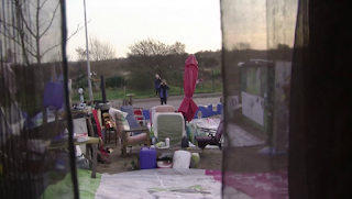 People standing in a furniture strewn yard of a house taking photos