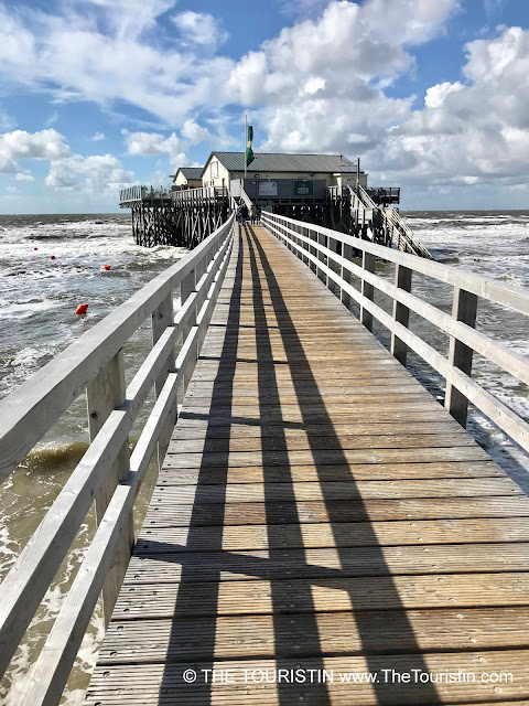 A wooden pier over the sea, leading to a white stilted cottage under a bright blue sky dotted with white clouds.