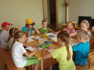 Nutraukoje, aplink stalą susėdę vaikai dalyvauja garsiniuose skaitymuose Labardžių bibliotekoje