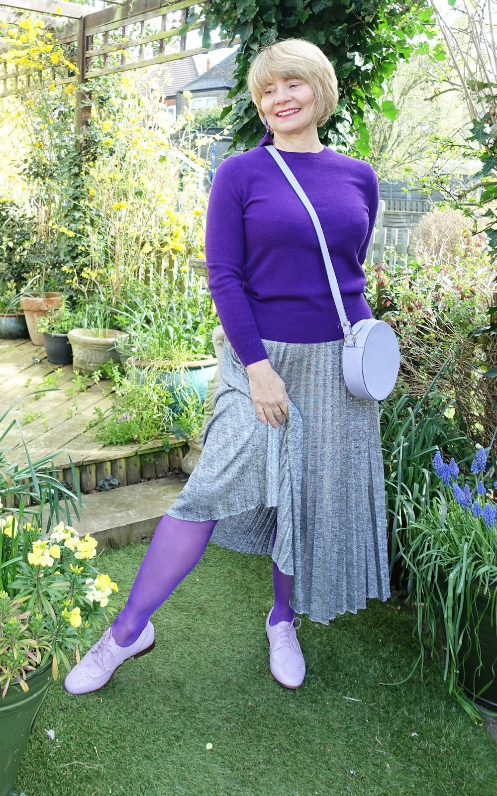 Instead of pairing white trainers with a long skirt, try a pair of distinctive brogues.  Lilac brogue shoes worn with a silver pleated skirt and purple tights and jumper.