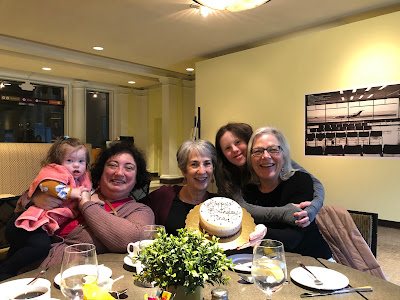 Four women and a toddler smiling at a cafe table; the toddler (far left, held by her mother) and young woman (right, standing between her mother and godmother) both have Down Syndrome.