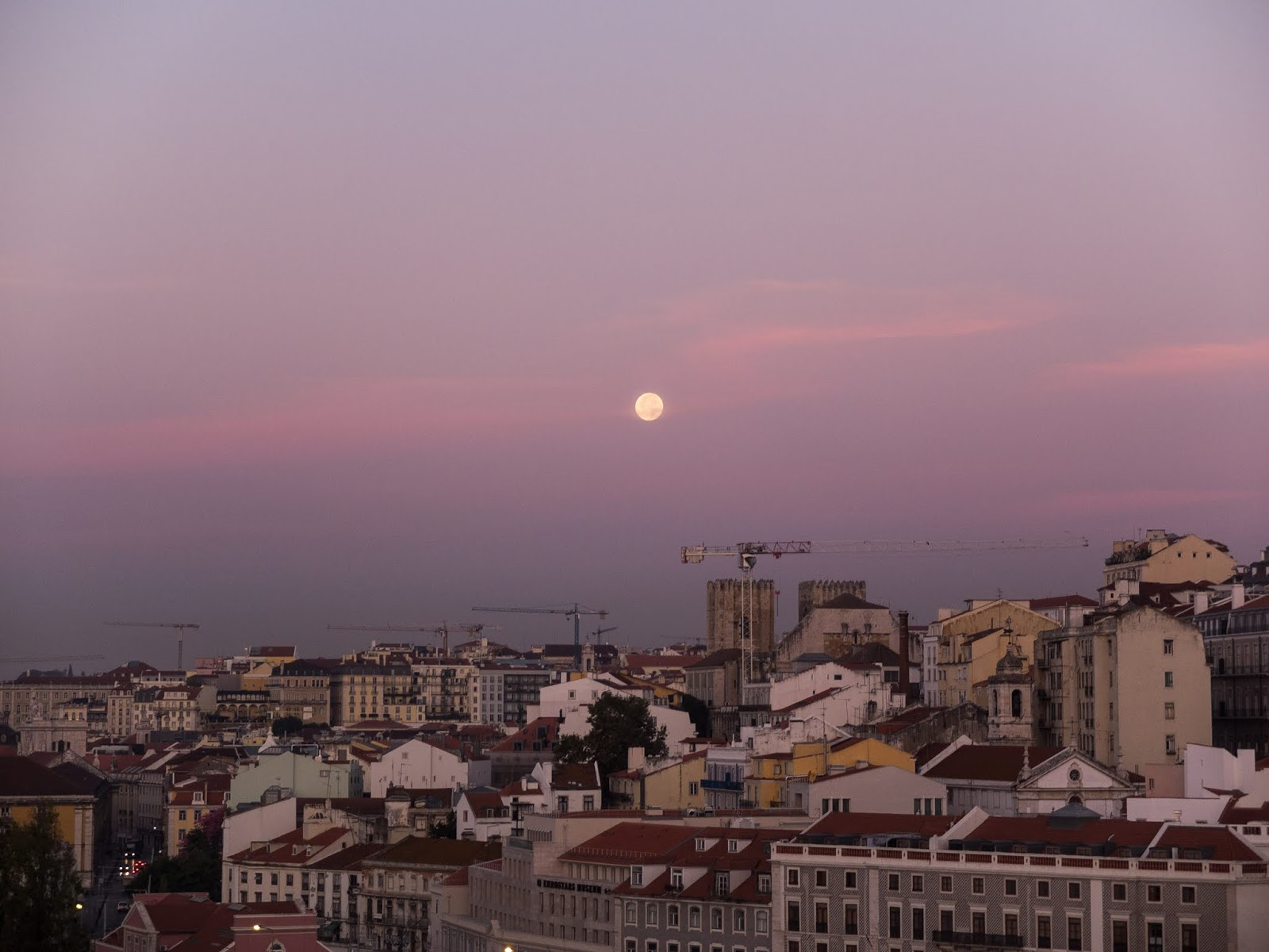 The moon over the city of Lisbon at dawn against a purple and pink sky.