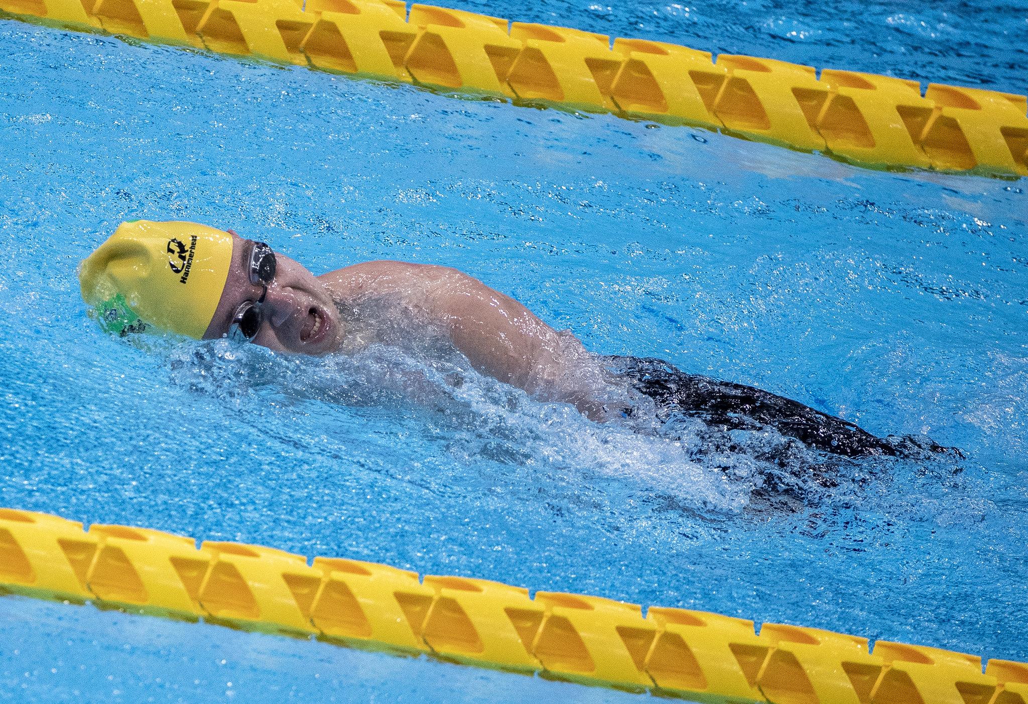 Bruno Becker, de touca amarela e de lado na piscina