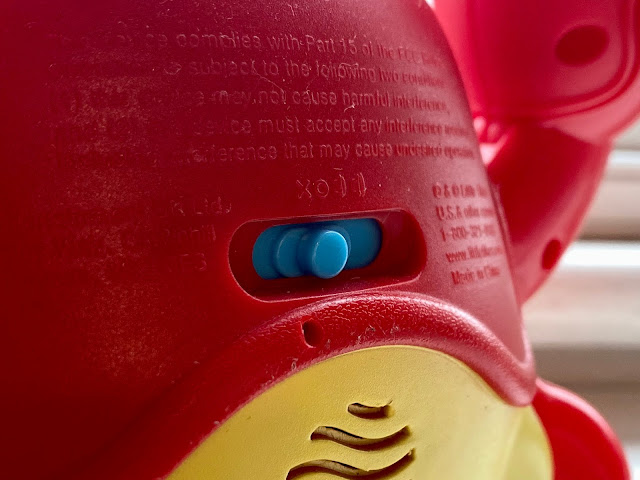 A close up of a red and yellow plastic Little Tikes crab with a on and off switch